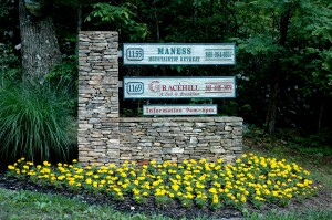 Newly planted marigolds at the base of the sign at the bottom of the driveway